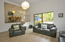 The living room has a comfy leather lounge, large flat screen television, and an ipod/ipad docking station.