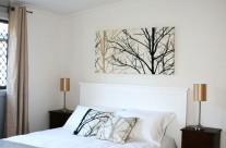 The master bedroom has a queen sized bed and is cosy and bright, tastefully decorated in natural tones.